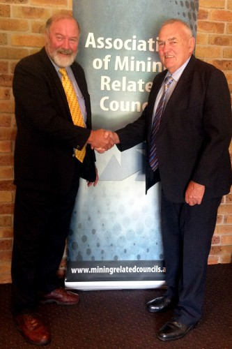 The Association on Mining Related Councils' new Chair, Mayor of Warrumbungle shire Council, Peter Shinton congratulated by outgoing chair, Cr. Col Mitchell of Wollondilly Shire Council.
